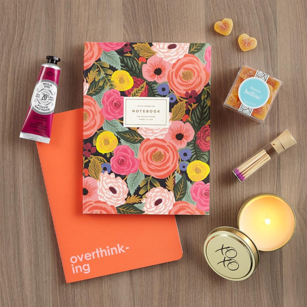 Gift set with two pretty notebooks, fig-scented shea butter hand cream, Hugs and Kisses XOXO candle, and Sugarfina's Peach Bellini Hearts
