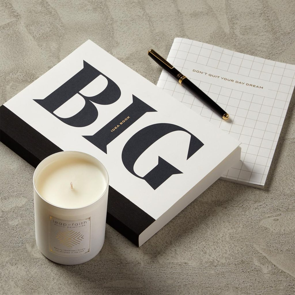 Large and small notebooks, candle, and roller ball pen