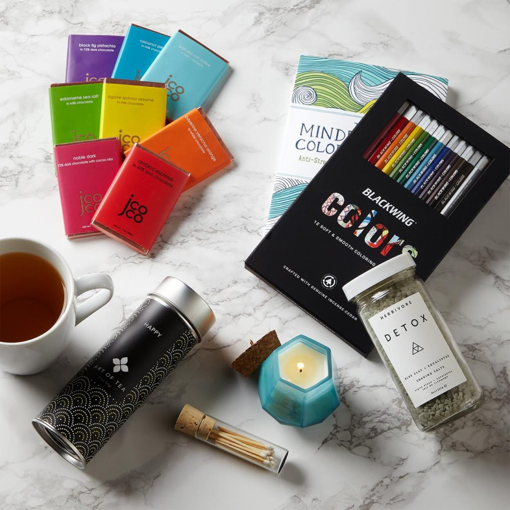 """Mindfulness Coloring Book - Anti-Stress Art Therapy for Busy People Blackwing Coloring Pencils, 12 count jcoco Mini Chocolate Bar Assortment, 8 flavors, 1 oz each Art of Tea Happy Loose Leaf Green Tea, 2.5 oz tin Herbivore Botanicals Detox Bath Salts, 8 oz bottle Paddywax Prism Glass Candle in Morning Dew, 2.75"""" h (without cork lid) x 3.5"""" w (at base) Vial of Mini Matches, white"""