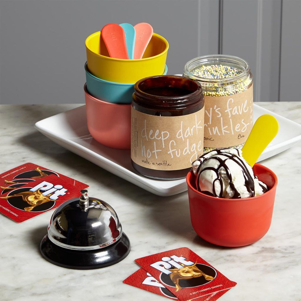 Gift set with fudge and sprinkles, colorful plastic bowls and spoons, and the game of Pit - just add ice cream