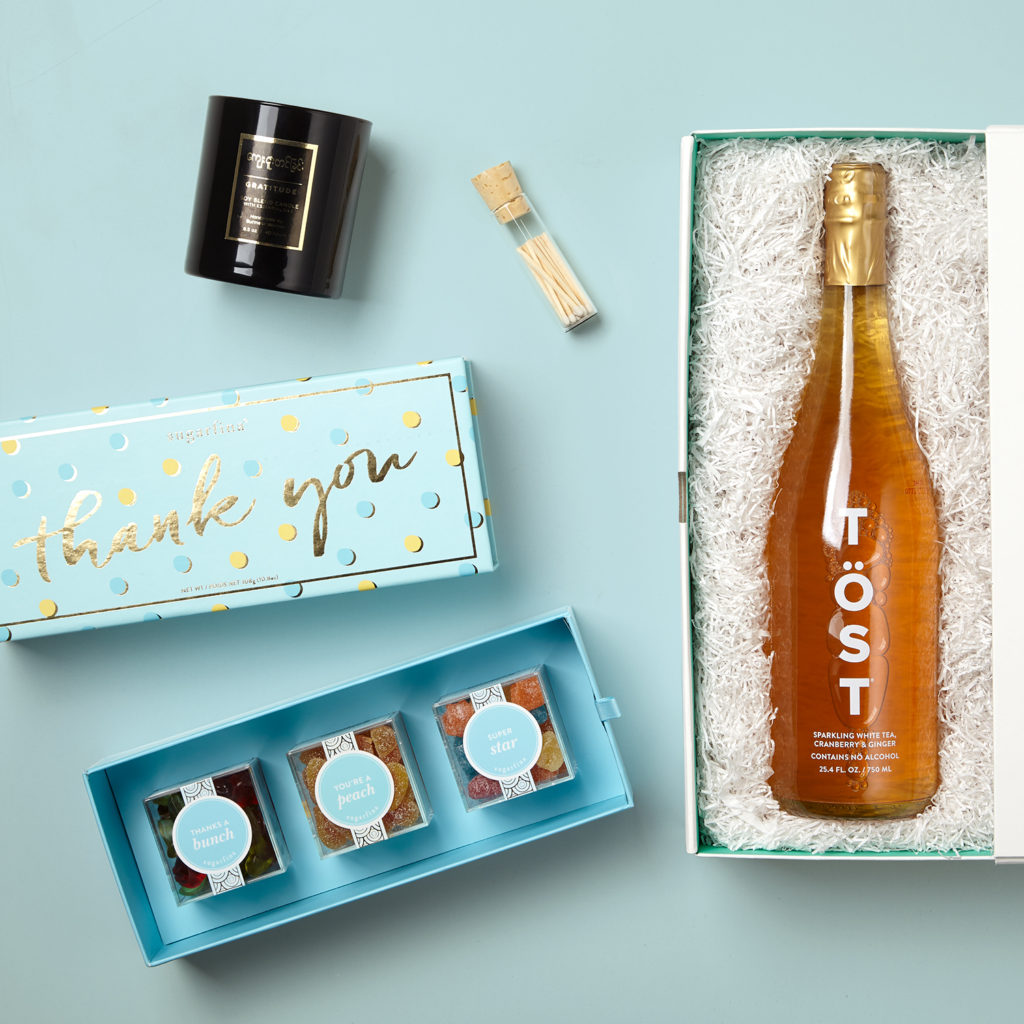 TÖST Non-Alcoholic Sparkling Beverage, Sugarfina Thank You Bento Box with 3 boxes of gourmet candy, Burmese Gratitude Candle from Prosperity Candle, white-tipped Mini Matches from Knack