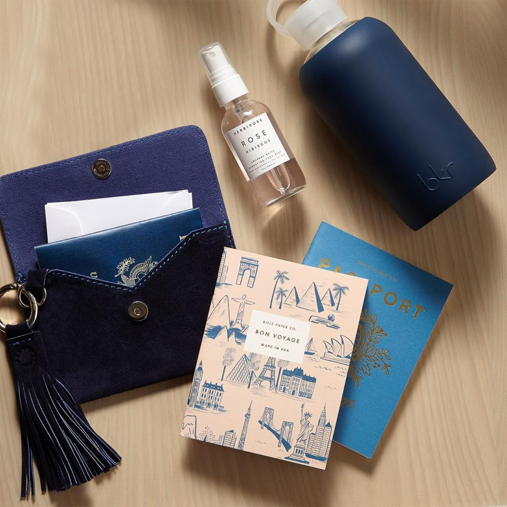 Mer-Sea Travel Luxe Navy Suede Passport Clutch, Rifle Paper Co. Bon Voyage Notebook, Set of 2, 64 pages each, bkr Fifth Ave Blue Original Glass Bottle, Herbivore Botanicals Rose Hibiscus Coconut Water Facial Mist