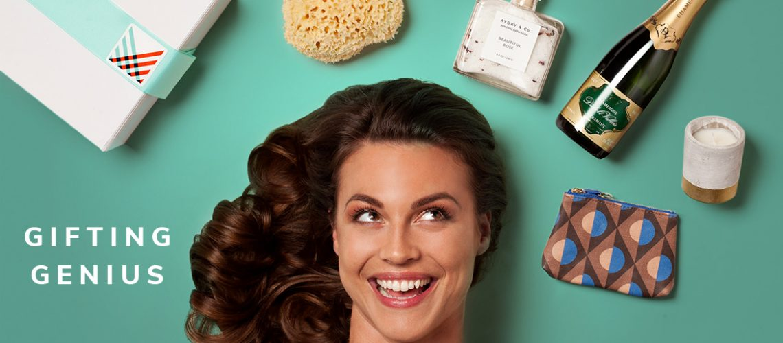 Smiling woman looking at gift products including bath salts, clutch purse, candle and champagne