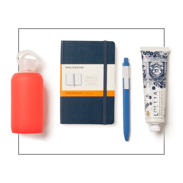 A coral pink BKR water bottle and blue Moleskine journal with a clip-on pen and Lollia shea butter handcreme