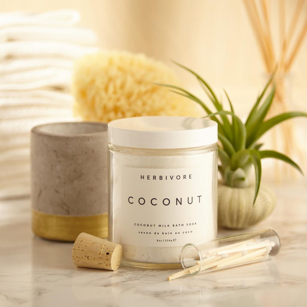 Gift set with coconut bath salts, a scented candle, sea sponge, and succulent air plant