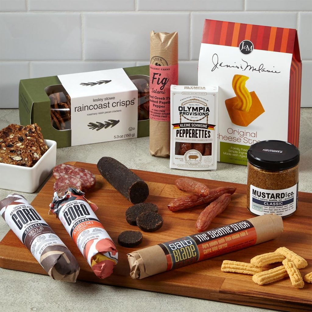 This unique client gift includes Olympia Provisions Kleine Schweine Pepperettes, Coro by Salumi Molé Salami 5 oz, Coro by Salumi Agrumi Salami 5 oz, Mustard and Co. Classic Mustard 7 oz, Salt Blade The Seattle Stick 3.8 oz, Hellenic Farms Smoked Paprika Fig Salami 6.4 oz, Janis & Melanie Cheese Straws 6 oz, and Raincoast Rosemary Raisin Pecan Crisps 5.3 oz