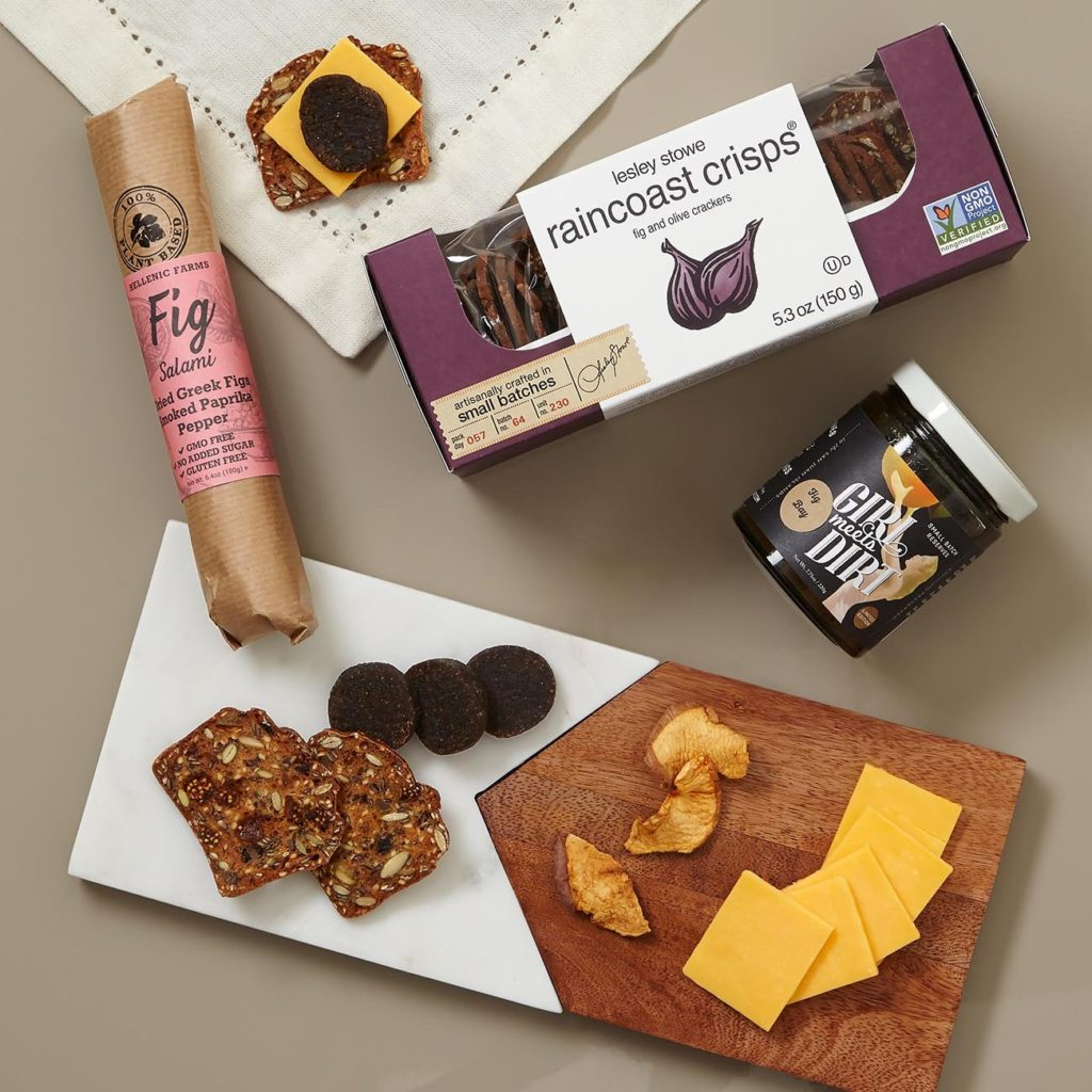 This unique client gift includes Girl Meets Dirt Fig Spoon Preserves, Raincoast Crisps Fig & Olive Cracker Crisps, Hellenic Farms Smoked Paprika Fig Salami, and Be Home Marble and Wood Cheese Board