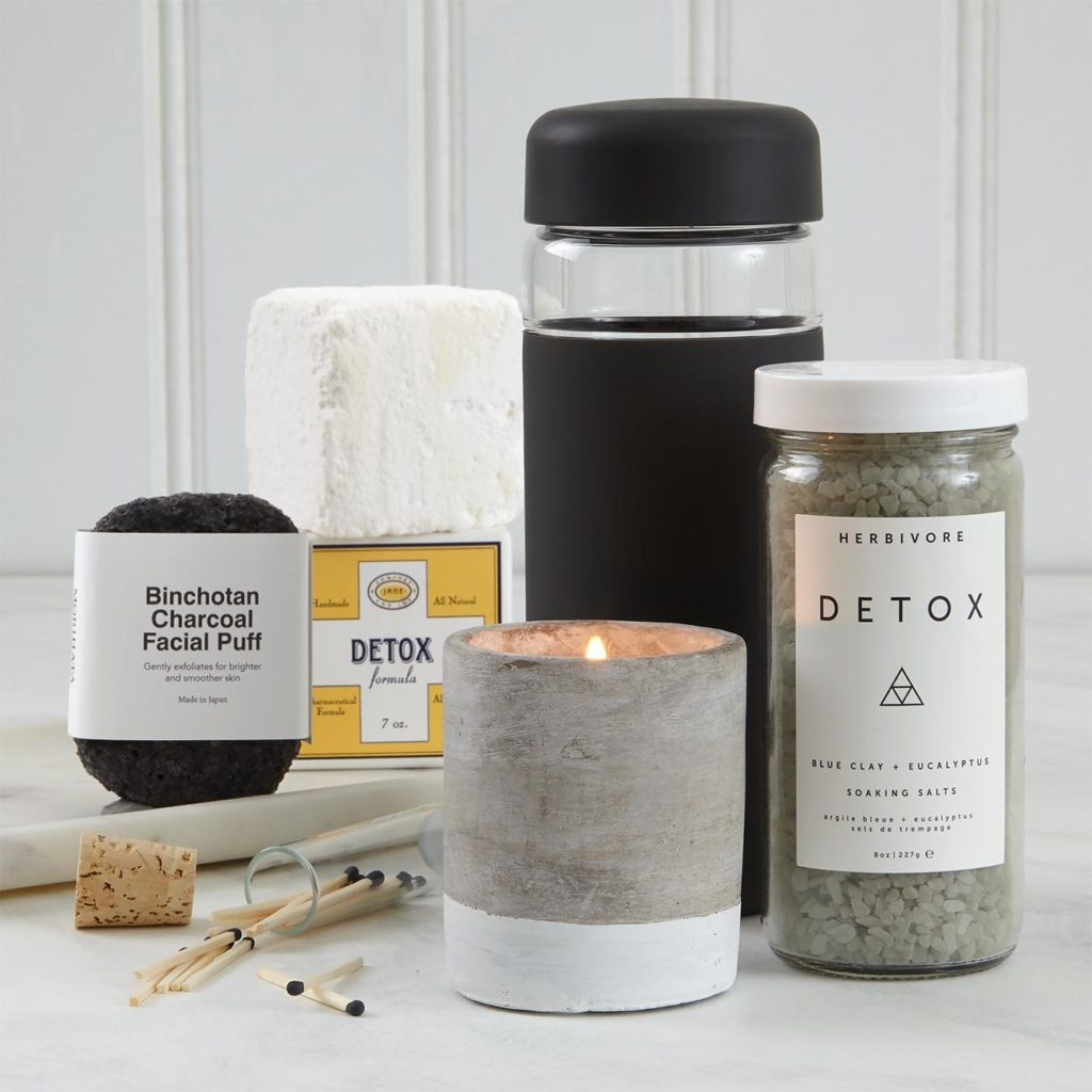 Herbivore Botanicals Detox Bath Salts,Jane Inc. Detox Bath Cube, Binchotan Charcoal Facial Puff, Paddywax Urban Concrete Candle in tobacco and patchouli, W & P Porter Wide Mouth Glass Bottle in Charcoal, Vial of black tipped matches