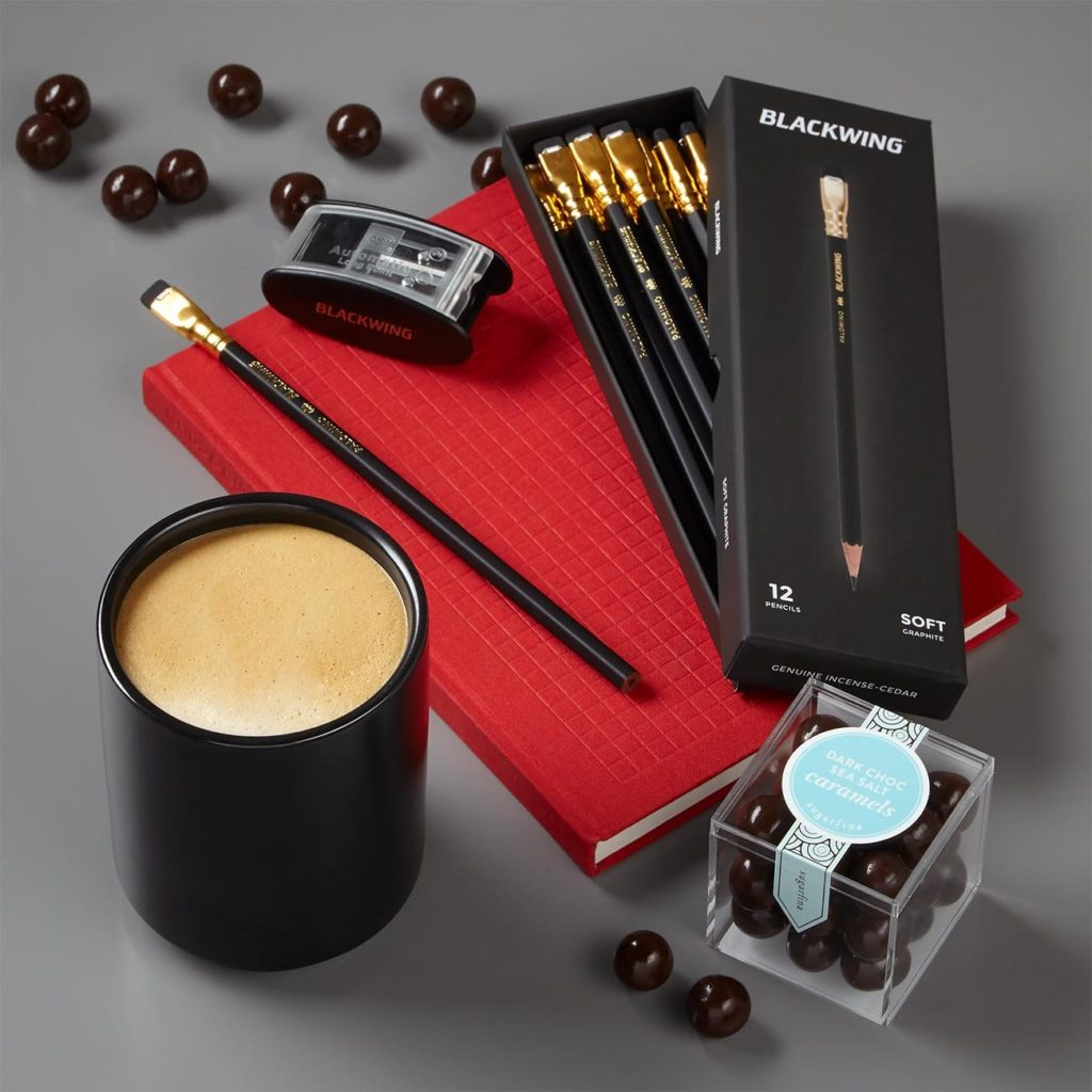 Princeton Architectural Press Grids & Guides Notebook, Palomino Blackwing pencils, Palomino Long Point Pencil Sharpener, Fellow Monty Matte Black Ceramic Latte Cup, and Sugarfina Dark Chocolate Sea Salt Caramels