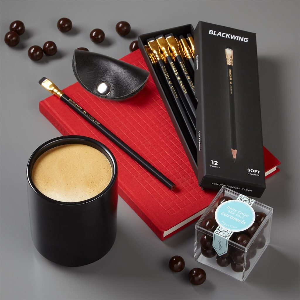 "This unique client gift includes Princeton Architectural Press Grids & Guides Notebook, Palomino Blackwing pencils, box of 12, each 8"" long, Coal Creek Leather Cord Wrap, 1.5"" h x 2.75"" w, Fellow Monty Matte Black Ceramic Latte Cup, max fill 11 oz, Sugarfina Dark Chocolate Sea Salt Caramels, net wt 2.7 oz, approx. 25 pieces"